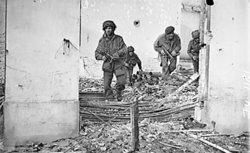 Four British paratroopers moving through a shell-damaged house in Oosterbeek during Operation Market Garden