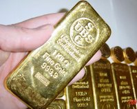 Gold bars with Krugerrands in the background.